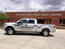 Image of a pick-up truck with decals reading San Juan County sheriff department. Truck sits in front of the public safety building in Monticello, Utah